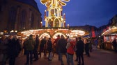 víkend : HEIDELBERG, GERMANY - DECEMBER 12, 2018: crowd of tourists at the Christmas market stand near the tables on background of illuminated food stalls and wooden shops in the evening