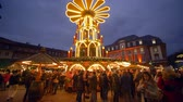 arife : HEIDELBERG, GERMANY - DECEMBER 12, 2018: people visit the traditional Christmas market with illuminated food stalls and wooden shops in the evening