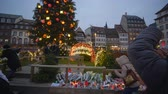 lembrar : STRASBOURG, FRANCE - DECEMBER 18, 2018: indifferent people are photographed on smartphone near Christmas tree and Flowers and candles in memory of victims terrorist attack at European city street Vídeos