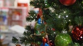 сувениры : HEIDELBERG, GERMANY - DECEMBER 12, 2018: Christmas gifts with candy in shop window and beautiful holiday artificial tree dressed up with colored toys and glittering garlands close-up in unfocused