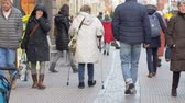 инвалид : HEIDELBERG, GERMANY - DECEMBER 12, 2018: old granny on crutches with sore feet walking down street and disappears into crowd passersby people in town
