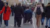 chory : HEIDELBERG, GERMANY - DECEMBER 12, 2018: sick tourist man is disabled on wheelchair walking on city street among crowd of passersby people
