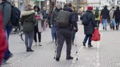 inválido : HEIDELBERG, GERMANY - DECEMBER 12, 2018: sick woman tourist with leg handicapped using crutches walking with backpack down street among crowd of people in city Vídeos