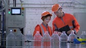 egyenlő : Engineers guy and girl into helmet and working clothes near conveyor line for bottling mineral water in plastic bottles during inspection and quality control of production at plant.