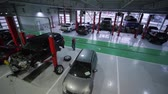 KHERSON, UKRAINE - FEBRUARY 26, 2019: car repair, lot cars on lifts and on floor during maintenance and technicians walk during work in large workshop, top view