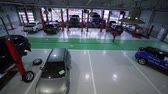 KHERSON, UKRAINE - FEBRUARY 26, 2019: car service station, many automobile on lifts and on floor during repair and technicians walk during work in large workshop, top view