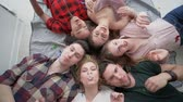 chicle : top view of happy friends lying on back blowing bubble gum together and smile at the camera during a home party Archivo de Video