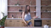 dona de casa : General cleaning, crazy housewife female with broom plays like guitar during household chores on cuisine