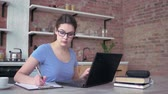 freelancer girl in eyeglasses typing on a laptop keyboard and writes notes in clipboard during online working sitting at the table at home