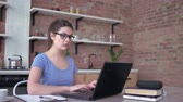 young woman in eyeglasses writes notes in clipboard during working or studying online in laptop computer at home