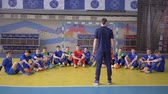 KHERSON, UKRAINE - APRIL 02, 2019: team spirit, trainer gives instructions for teenagers football players before match at sports hall