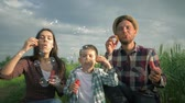 verificador : beautiful young family blown a great many bubbles in slow motion, parents with son in plaid shirts have fun outdoors sitting at green field on background of sky