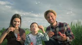 verificador : family blowing soap bubbles and laughing in slow motion, little boy with mum and daddy in plaid shirts have fun during weekend at green meadow