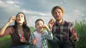 verificador : portrait of young family playing with soap bubbles outdoors, child with mom and dad in checkered shirts have fun time in green field on background of sky