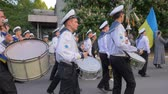 street parade : KHERSON, UKRAINE - MAY 20, 2019: Festival Melpomene of Tavria, marching band on parade, young sailors in white uniform play on big drums and carry Ukrainian flag at the street in slow motion