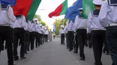 KHERSON, UKRAINE - MAY 20, 2019: Festival Melpomene of Tavria, sailors dressed in uniform go with colorful flags and musical instruments on the street at the parade Vídeos
