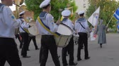 KHERSON, UKRAINE - MAY 20, 2019: Festival Melpomene of Tavria, sailors in uniform play on musical instruments during the march on parade and carry different flags at the street