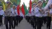 KHERSON, UKRAINE - MAY 20, 2019: Festival Melpomene of Tavria, sailors of Marine Academy in uniform play on musical instruments during the march and carry colorful flags on parade at the street Vídeos