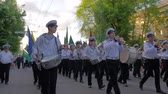 KHERSON, UKRAINE - MAY 20, 2019: Festival Melpomene of Tavria, sailors students in uniform play musical instruments and carry multicolored flags during the parade in the street