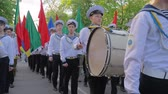 KHERSON, UKRAINE - MAY 20, 2019: Festival Melpomene of Tavria, students of Marine Academy march on a parade with multicolored flags in their hands, a young sailor with sticks close-up beats the big drum