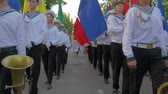 KHERSON, UKRAINE - MAY 20, 2019: Festival Melpomene of Tavria, young sailors in uniform with sticks in hands play on big drums during the march and carry colorful flags at street, girl in parade waving hands at camera Vídeos