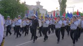 KHERSON, UKRAINE - MAY 20, 2019: Festival Melpomene of Tavria, parade of sailors, young men dressed in uniform play musical instruments and carry in hand flags of different colors walking down a crowded street