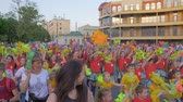 festividades : KHERSON, UKRAINE - MAY 20, 2019: Festival Melpomene of Tavria, holiday summer festival, many children and teenagers in bright clothes waving hands and shouting chants on city street