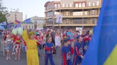 多民族の : KHERSON, UKRAINE - MAY 20, 2019: Festival Melpomene of Tavria, crowd of adults and children in suits with flags in hands are walking along city street during festive festival 動画素材