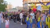 多民族の : KHERSON, UKRAINE - MAY 20, 2019: Festival Melpomene of Tavria, National parade, crowd youth in different costumes with Ukrainian flags walk along city street and shout chants on open air