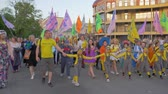 多民族の : KHERSON, UKRAINE - MAY 20, 2019: Festival Melpomene of Tavria, happy crowd of people of different ages in bright costumes with colored flags walking down city street during festival in summer 動画素材