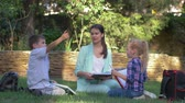 učitel : elementary school, happy schoolkids boy and girl with tutor woman read classbook and chat during training on grass outdoors