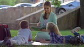 učitel : extracurricular activities, cute kids listening to woman reading book after school sitting on green grass in nature in sunny light close-up after school lessons
