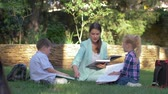 učitel : modern education methods, classmate pupils boy and girl with tutor female read schoolbook and chat during lesson on lawn outdoors Dostupné videozáznamy