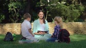 učitel : young teacher woman holds lesson outdoors for little boy and girl with books in hands while sitting on green grass