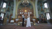 KHERSON, UKRAINE - JUNE 04, 2019: marriage ceremony, Loving guy and girl into white wedding dress with candles in hands look into each other eyes during wedding ceremony at church altar with icons Vídeos