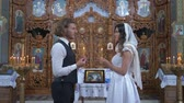 KHERSON, UKRAINE - JUNE 04, 2019: nuptial ceremony in church, young fiancee and bridegroom with candles in hands look into each other eyes during marriage ceremony at altar with icons