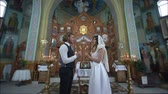 алтарь : KHERSON, UKRAINE - JUNE 04, 2019: rite of marriage in church, young believers groom and fiancee with candles in hands stand at orthodox temple during wedding ceremony among icon