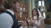 KHERSON, UKRAINE - JUNE 04, 2019: wedding church ceremony, happy smiling newlyweds with candles in hands look into each other eyes during marriage ceremony at altar with icons