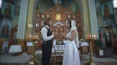 nupcial : KHERSON, UKRAINE - JUNE 04, 2019: wedding day in church, Loving man and woman into white wedding dress with candles in hands look into each other eyes during marriage ceremony at altar with icons