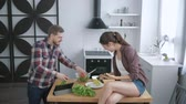 hasznos : crazy family, funny cheerful man is fooling around and making grimaces with vegetables and woman takes picture on smartphone while sitting on table in kitchen while cooking healthy food for lunch