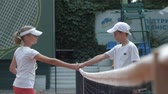 서브 : KHERSON, UKRAINE - JUNE 09, 2019: competitive spirit, ambitious tennis players boy and girl shake hands while greeting each other near net before match on court and walking on positions