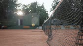 mecz : KHERSON, UKRAINE - JUNE 09, 2019: Yellow tennis ball hit net and bounces back on red court close up in slow motion on open air