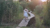 dinlenmek : children games, happy little boy and girl play catch-up and run on wooden bridge among green high reeds Outdoors