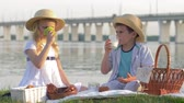 mléčný výrobek : lovely hungry kid girl and boy in straw hats eat sweet bakery products and drink fresh milk during picnic in nature near river in sunlight