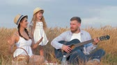 klappen : countryside family leisure, young man plays guitar while his beautiful wife and cute little daughter dance laughing at picnic with milk and buns in grain harvest field of golden wheat shining by sunbeams Stockvideo