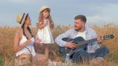 klappen : family fun in nature, young cheerful daddy plays guitar when his beautiful wife and little pretty daugther clap hands happily dancing during picnic in shining by sunbeams wheat harvest field