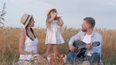 botella de leche : family in countryside picnic, little tender girl drinks milk from bottle during outings with her young mother and happy dad playing guitar in sunny reaped wheat field at harvest time Archivo de Video