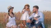 klappen : family countryside recreation, young dad plays guitar when his woman in straw hat and white dress dances clapping hands and snapping fingers while their little girl kid eating sweet bun in golden grain field picnic