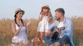 klappen : family outdoor holidays, young daddy plays guitar while his beautiful wife claps hands and their little daughter in straw hat and white dress eats sweet baked bun at open air picnic in sunny grain harvest wheat field Stockvideo