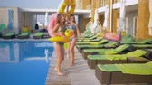 kilépő : happy attractive girlfriends into bathing suit with Inflatable rings walk near blue pool during summer holiday at luxurious resort